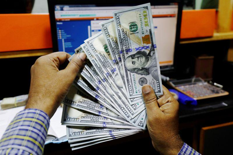 Dollar eases on defiant economic hopes, negative rates spectre
